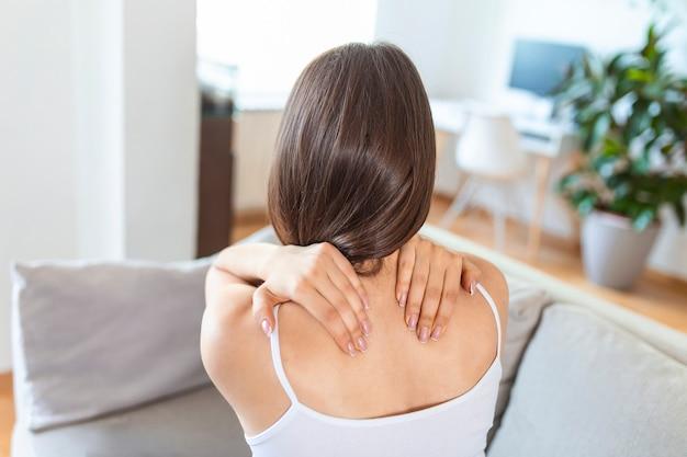 Молодая женщина страдает от боли в спине дома. портрет молодой девушки брюнетки, сидящей на диване у себя дома с болью в шее и спине. красивая женщина, имеющая боль в позвоночнике или шее