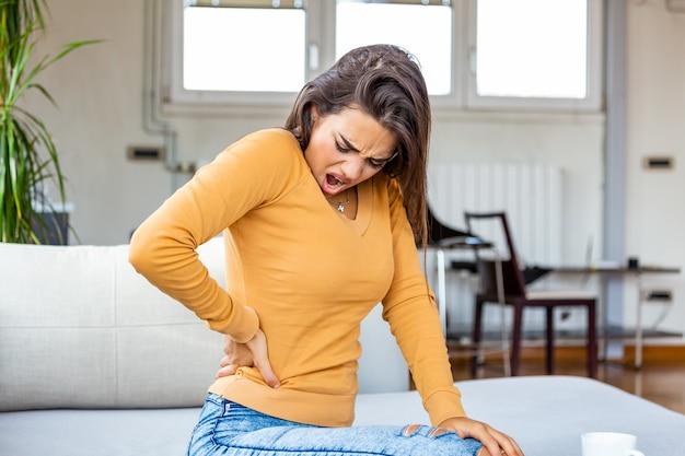 自宅で腰痛に苦しんでいる若い女性。頭痛と背中の痛みで自宅のソファに座っている若いブルネットの女性の肖像画。