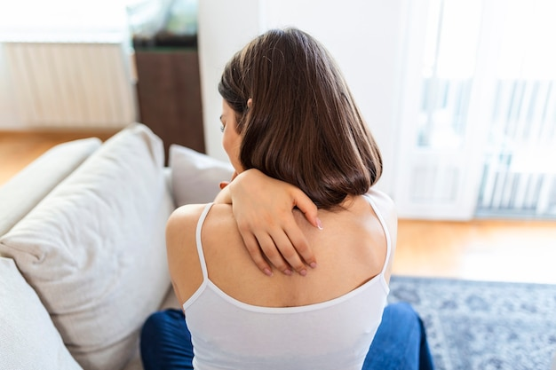 Young woman suffering from backache at home. portrait of a young brunette girl sitting on the couch at home with a neckache and back pain. beautiful woman having spinal or neck pain