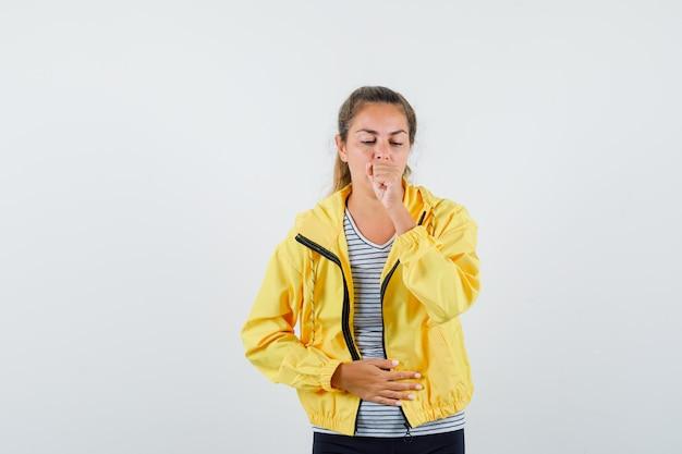 Tシャツ、ジャケット、体調不良の咳に苦しんでいる若い女性。正面図。