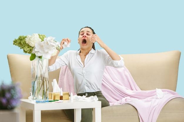 家庭のほこりや季節性アレルギーに苦しんでいる若い女性。ナプキンでくしゃみをし、床とソファで使用済みナプキンに囲まれて座っています。結果のない薬を服用している。ヘルスケアの概念。