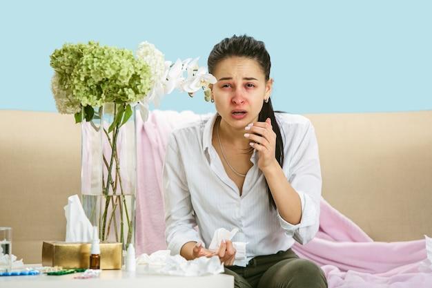 집 먼지나 계절 알레르기로 고통받는 젊은 여성. 냅킨에 재채기하고 바닥과 소파에 사용한 냅킨에 둘러싸여 앉아. 결과없이 약을 복용. 의료 개념입니다.