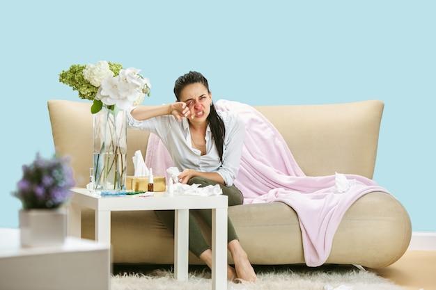 家庭のほこりや季節性アレルギーに苦しんでいる若い女性ナプキンでくしゃみ