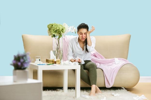 家庭のほこりや季節性アレルギーに苦しんでいる若い女性。