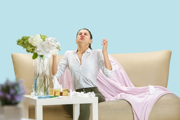 Young woman suffering from hausehold dust or seasonal allergy. sneezing in the napkin and sitting surrounded by used napkins on the floor and sofa. taking medicines with no result. healthcare concept.