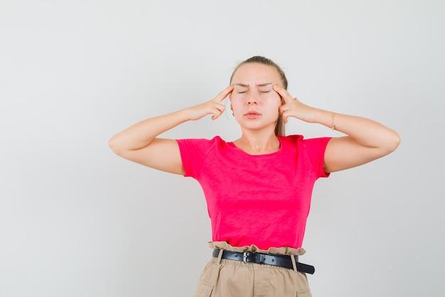 T- 셔츠와 바지에 두통으로 고통 받고 피곤 찾고 젊은 여자