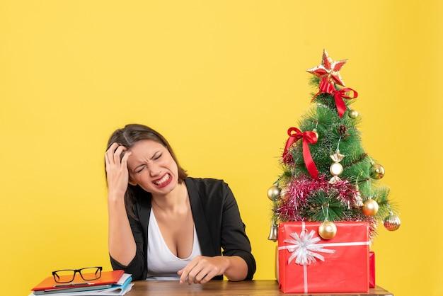 黄色のオフィスで飾られたクリスマスツリーの近くのスーツのテーブルに座って頭痛に苦しんでいる若い女性