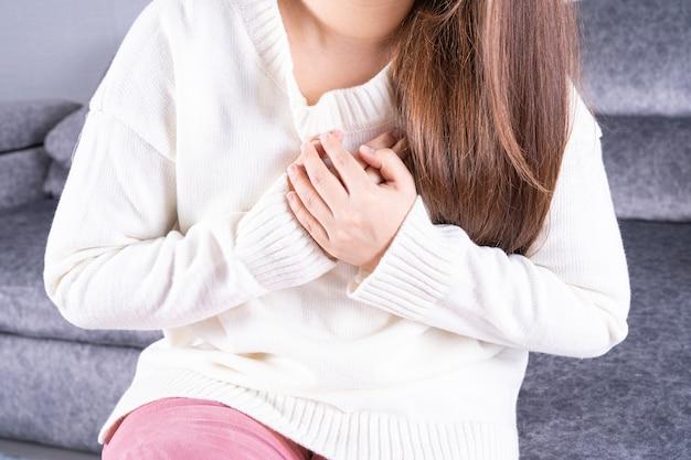 自宅のソファーに座っている間心の痛みに苦しんでいる若い女性