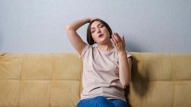 집에서 소파에 앉아 있는 동안 더위를 앓고 있는 젊은 여성.