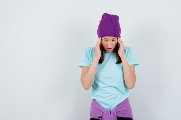 Giovane donna che soffre di emicrania in maglietta, berretto e dall'aspetto angosciato, vista frontale.