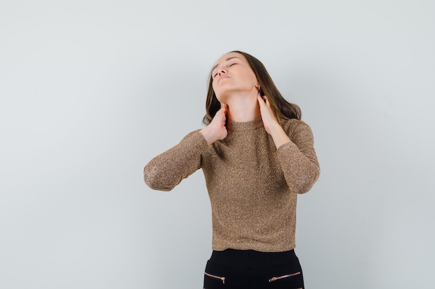 Giovane donna che soffre di dolore al collo in camicetta dorata e sembra turbata