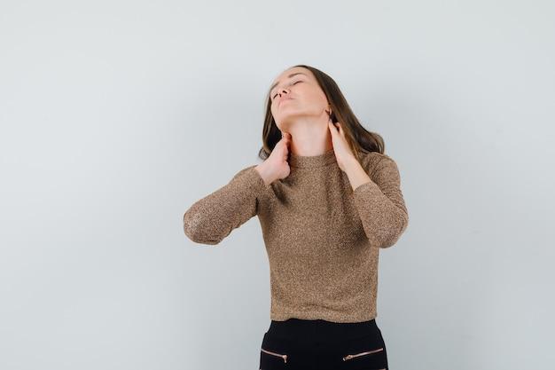 Молодая женщина в золотой блузке страдает от боли в шее и выглядит обеспокоенной