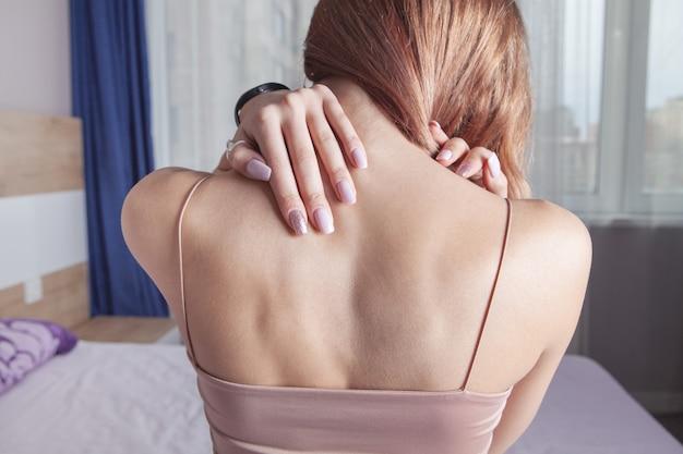 목 통증으로 고통받는 젊은 여자.