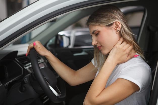彼女の車の運転席に座って、首のむち打ち症に苦しんでいる若い女性