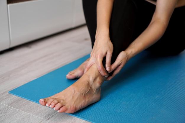 Молодая женщина страдает от боли в лодыжке или травме стопы, сидя на коврике для растяжки