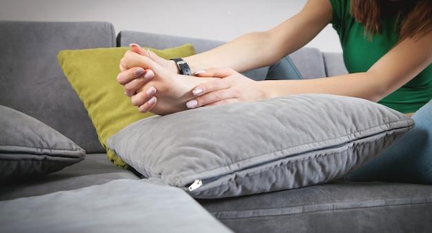 Молодая женщина страдает от боли в ноге.