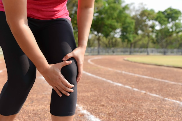 Young woman suffering from running knee or kneecap injury during outdoor workout.