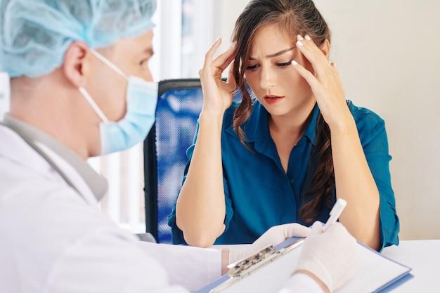彼の顔に医療マスクで彼女と話している医者を訪問して激しい頭痛に苦しんでいる若い女性