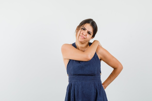 Young woman suffering from shoulder pain in dress and looking uncomfortable