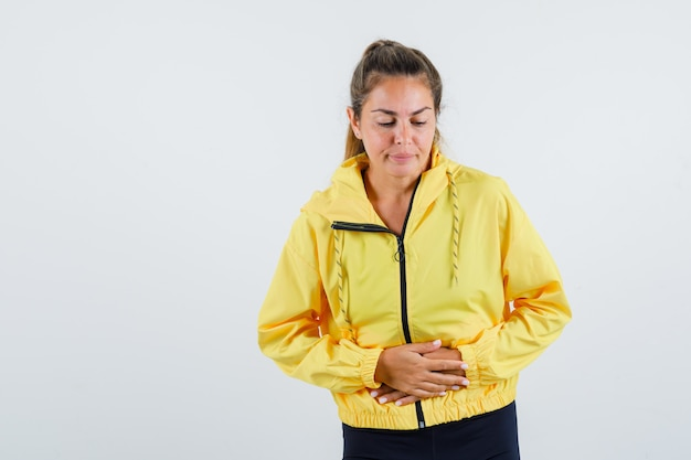 Young woman suffering from stomach ache in yellow raincoat and looking uncomfortable