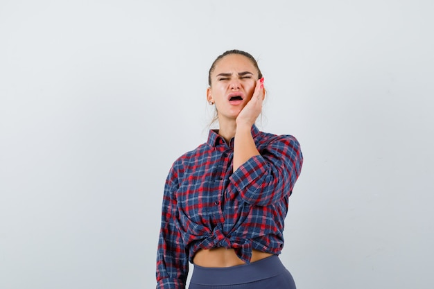 Young woman suffering from toothache in checkered shirt and looking painful , front view.