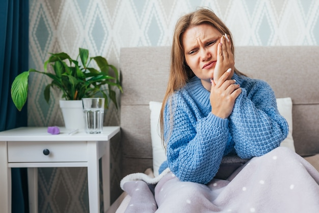 Young woman suffering from toothache while sit in bed at home.