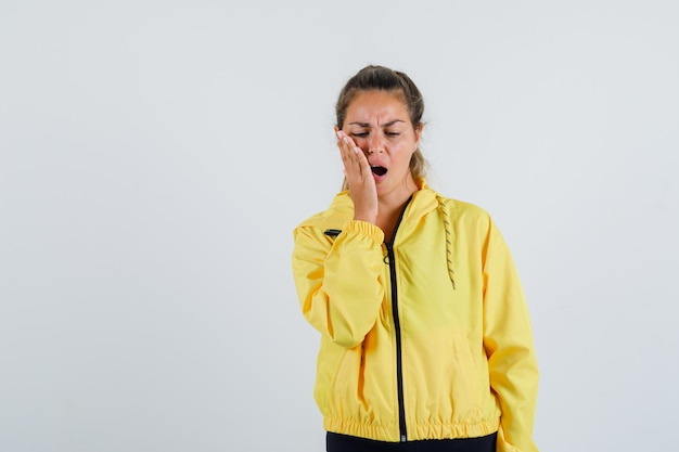 Young woman suffering from toothache in yellow raincoat and looking painful