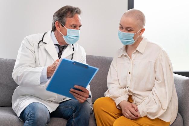 Молодая женщина, страдающая от рака груди, разговаривает со своим врачом