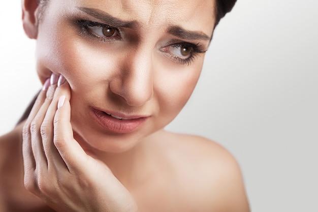 Молодая женщина страдает от ужасной боли в зубах