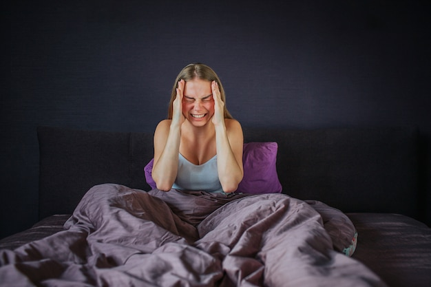 Young woman suffers from headache. she screams out loud. model holds hands close to forehead. her legs are covered with blanket. she sits on bed. young woman is alone.