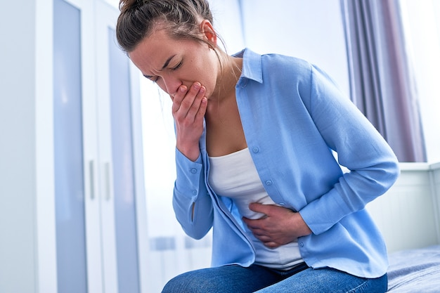 Young woman suffers from nausea and vomiting due to digestive and stomach illness problems