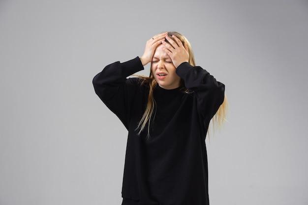 젊은 여성이 고통을 겪고 병이 나고 벽에 약점을 느낍니다.