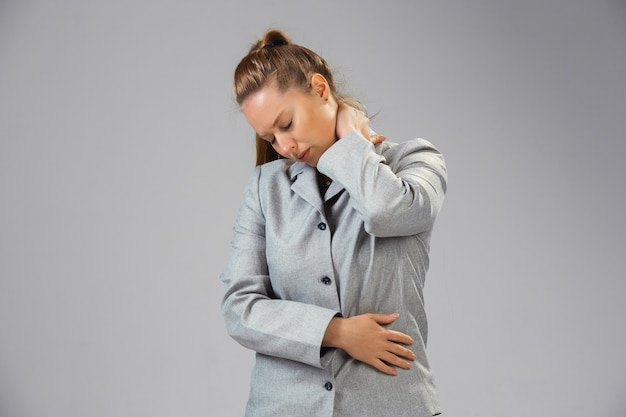 Young woman suffers from pain feels sick ill and weakness isolted on wall