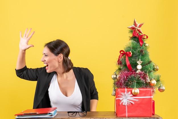Giovane donna in vestito che chiama qualcuno vicino all'albero di natale decorato in ufficio sul lato destro del giallo