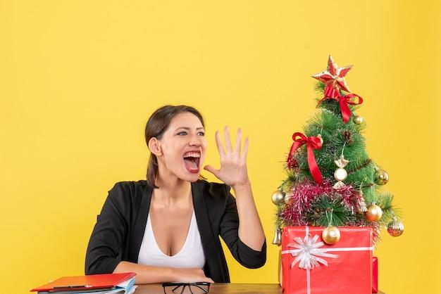 Giovane donna in tuta chiamando qualcuno vicino all'albero di natale decorato in ufficio su giallo