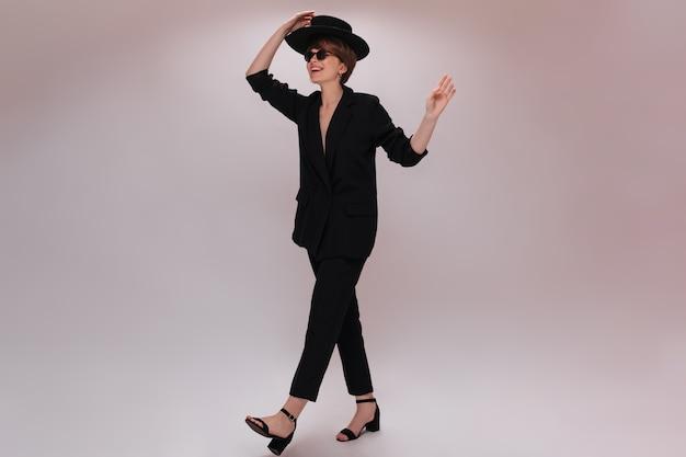 Giovane donna in tuta e cappello in movimento su sfondo isolato. attraente signora dai capelli corti in giacca nera e pantaloni ha una passeggiata su sfondo bianco