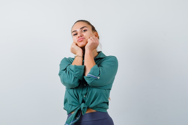 Young woman sulking with cheeks on hands in green shirt and looking pensive. front view.