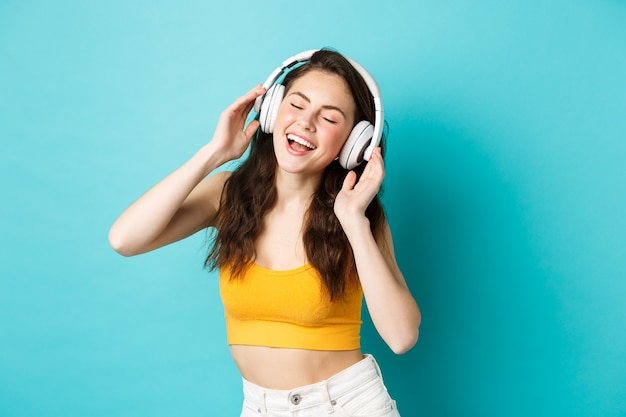 Young woman in summer clothes listening music, wearing headphones and singing along favorite song, dancing in earphones, standing against blue background.