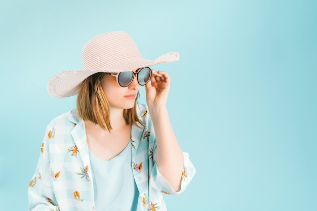 Young woman in summer clothes with pink straw hat and round glasses on light blue background