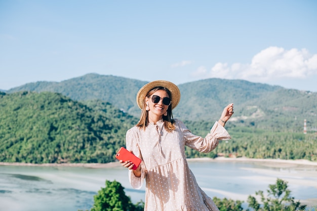 Young woman in summer cute dress, straw hat and sunglasses dancing with smartphone on hand