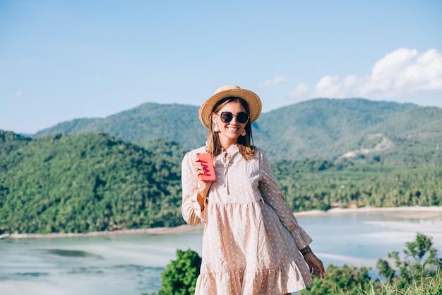 Giovane donna in abito carino estivo, cappello di paglia e occhiali da sole ballando con lo smartphone a portata di mano