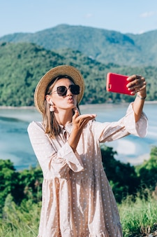 Young woman in summer cute dress, straw hat and sunglasses making videocall with her smartphone