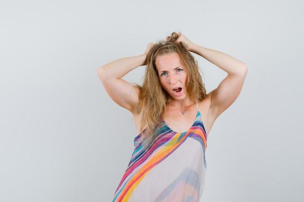 Giovane donna in abito estivo in posa con le mani sulla testa e sembra pazza