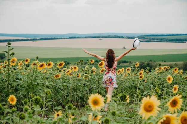 A young woman in a summer dress runs in a field with sunflowers spread her arms to the sides.