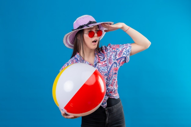 Young woman in summer hat wearing red sunglasses holding inflatable ball looking far away with hand looking for someone over blue wall