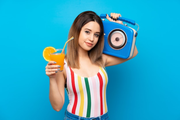 Young woman in summer holidays over blue wall with cocktail