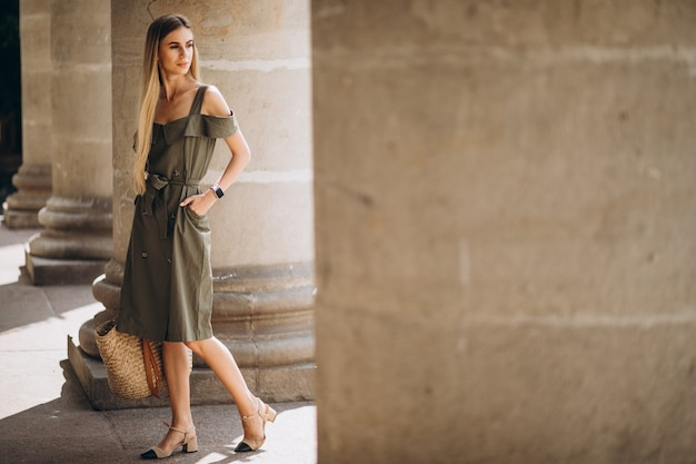Young woman in summer outfit by an old building