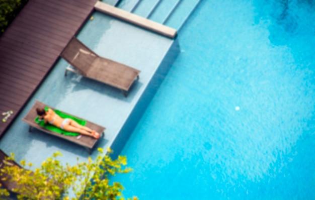 若い女性はプールでリラックスして日光浴