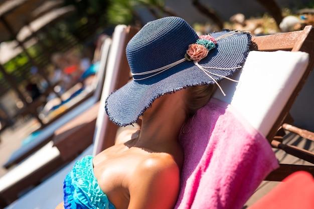 Молодая женщина, загорая у бассейна