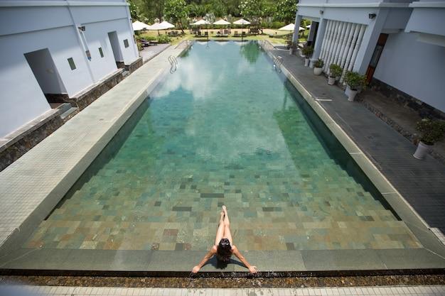 Young woman sunbathing in hotel swimming pool